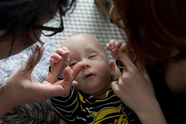 Viiden kuukauden ikäinen Toivo harjoitteli tarttumista äidin ja mummin sormiin.