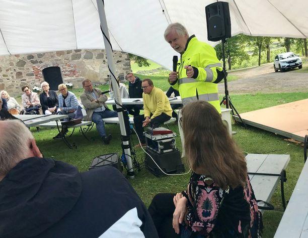 Tuomioja puhui Kuitian linnan tuulisella pihalla. Kartanon suojatakki oli tarpeen viileän ilmanalan vuoksi. Taustalla penkeille istumassa kartanonisäntä Ilkka Herlin sekä keskustan kansanedustaja Matti Vanhanen.
