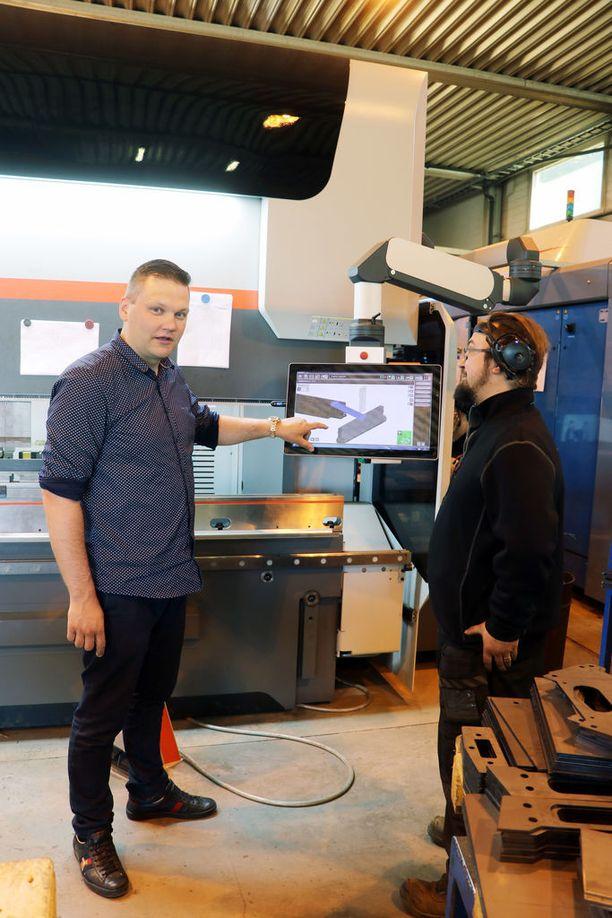 Petri Niinimäki (vas.) ja Mikko Virtala pystyvät pyörittämään uudella särmäyspuristimella käsiteltävän metallikappaleen näkyviin kolmiulotteisena, jotta tuote saa varmasti oikean muodon.