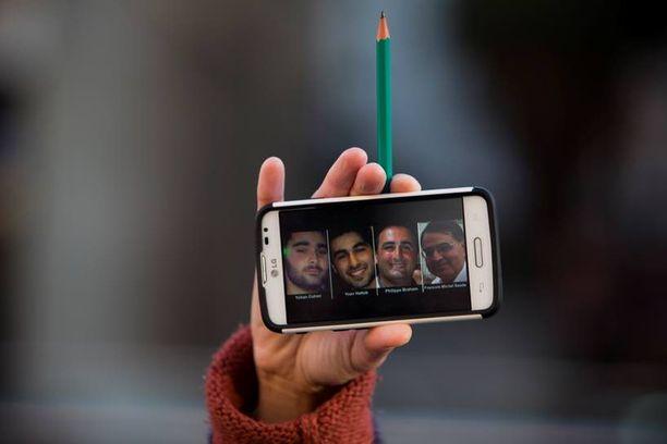 Nainen piti Tel Avivissa tukimielenosoituksessa kädessään kännykkää, jossa oli kuva supermarketissa kuolleista neljästä miehestä.