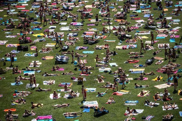 Ihmiset ottavat aurinkoa Prahassa, jossa lämpötilan odotetaan nousevan ainakin 38 asteeseen.