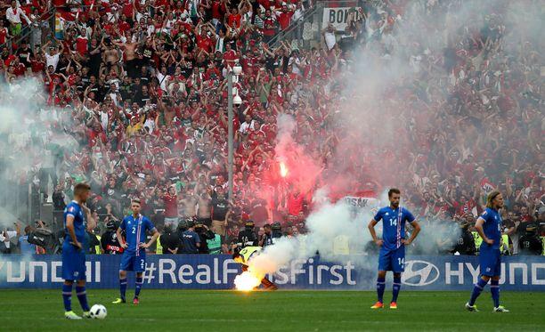 Islannin pelaajien pettymystä ei varmastikaan helpottanut katsojan kentälle heittämä soihtu.