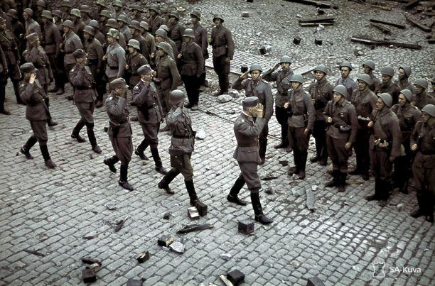 Kenraaliluutnantti Lennart Oesch tarkastaa joukot Torkkeli Knuutinpojan patsaalla Viipurin valtausparaatissa 31.8.1941. Valkoisia hihanauhoja ei enää näy.