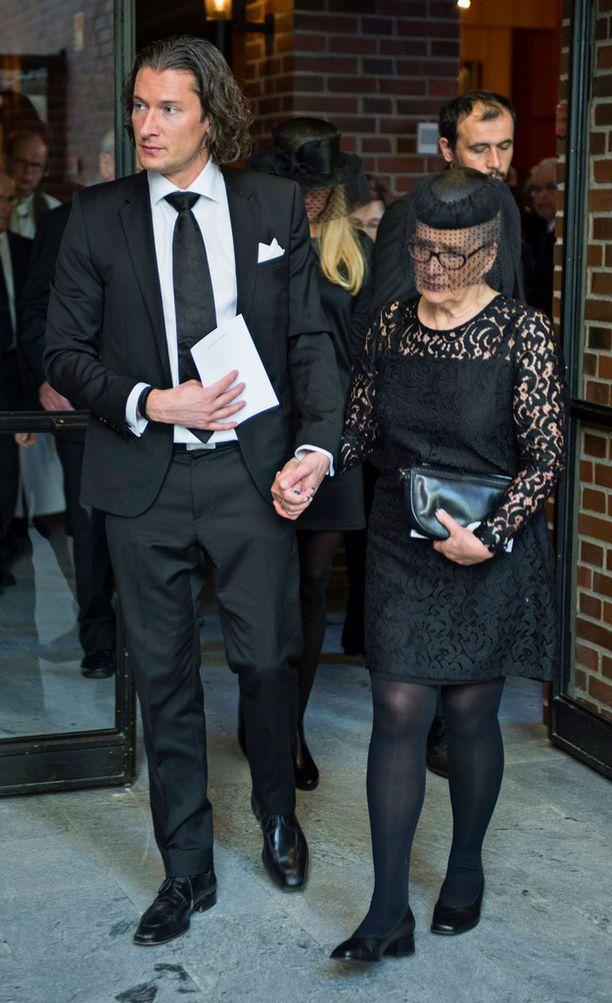 Tomi tuki äitiään Maikkia Martin hautajaisissa.