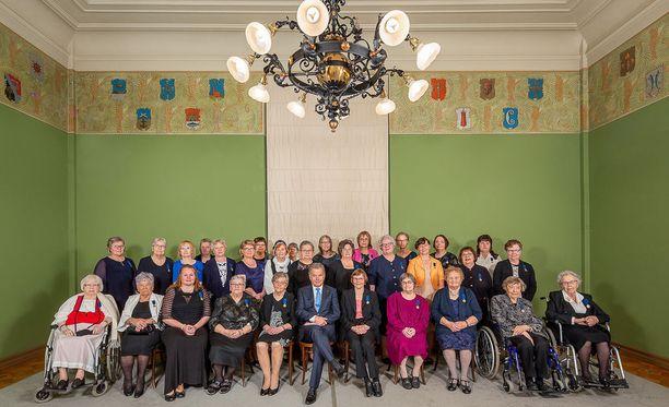 Palkitut äidit ikuistettiin ryhmäkuvaan tasavallan presidentin Sauli Niinistön kanssa. Tuula Savolainen istuu ensimmäisessä rivissä toisena vasemmalta lukien.