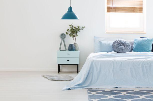 Siniset tekstiilit, matto, valaisin ja yöpöytä luovat uneliaan tunnelman.