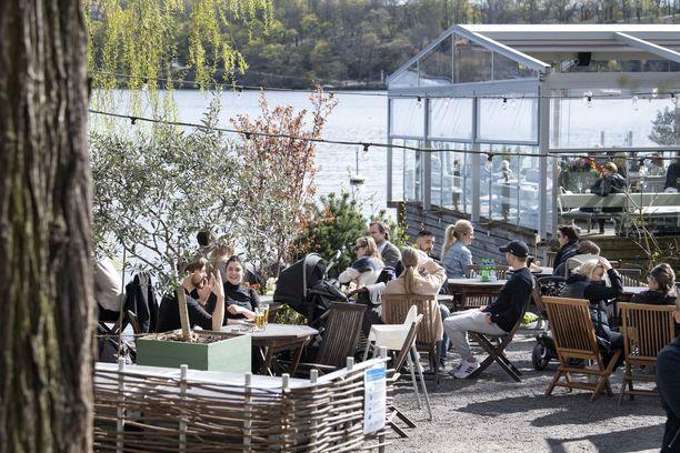 Tukholmalaiset nauttivat kauniista kevätsäästä ulkoilmaravintolassa. Ruotsin koronastrategia on eronnut muista maista.e