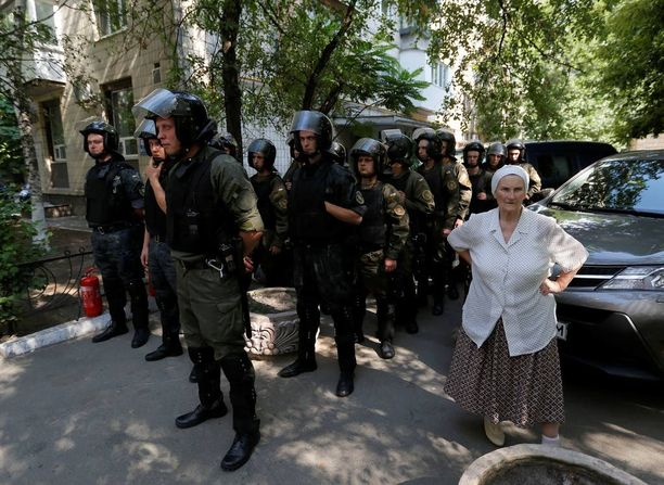 Mellakkapoliisit tarkkailivat korruption vastaisia mielenosoittajia, jotka vaativat Ukrainan valtakunnansyyttäjän Viktor Shokinin eroa.