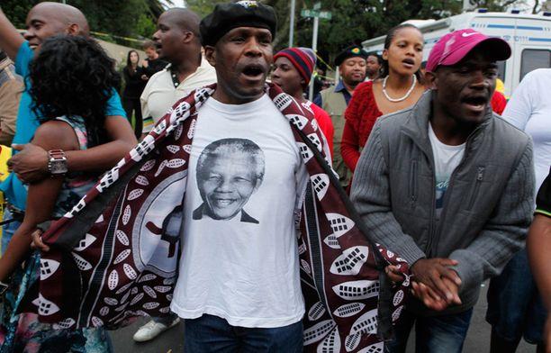 Ihmiset laulavat ja tanssivat Johannesburgin kaduilla.