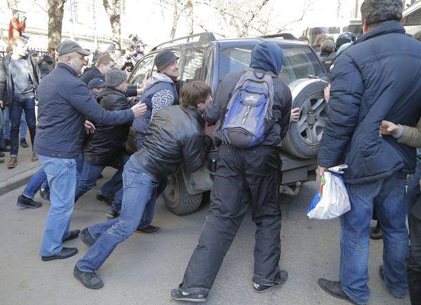 Ihmiset piirittivät poliisiauton, jonka sisään oppositiojohtaja Navalnyi sullottiin.