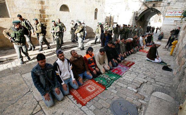 Muslimimiehiä rukoilemassa tiistaina lähellä Lions' Gatea, yhtä Jerusalemin vanhan kaupungin porteista. Israelin sotilaat partioivat taka-alalla.