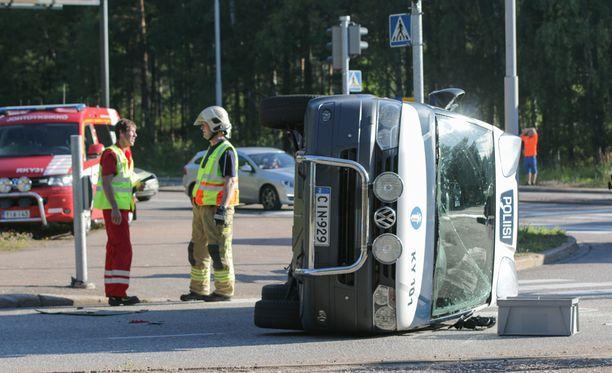 Törmäyksen seurauksena poliisiauto kaatui kyljelleen ja sen takarengas irtosi.