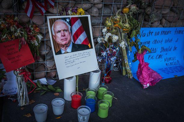 Ihmiset ovat tuoneet kukkia ja kynttilöitä McCainin toimisto ulkopuolelle Phoenixissä.