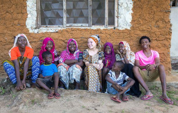 Violan perhe istumassa oman talon takana. Kuvassa Munira Juma (vasemmalta), Riziki Juma, Zawadi Salim, Viola Wallenius, Mesaidi Juma, Mapenzi Juma, Salim Mwarima. Edessä: Ali Juma ja Mohammed Juma.