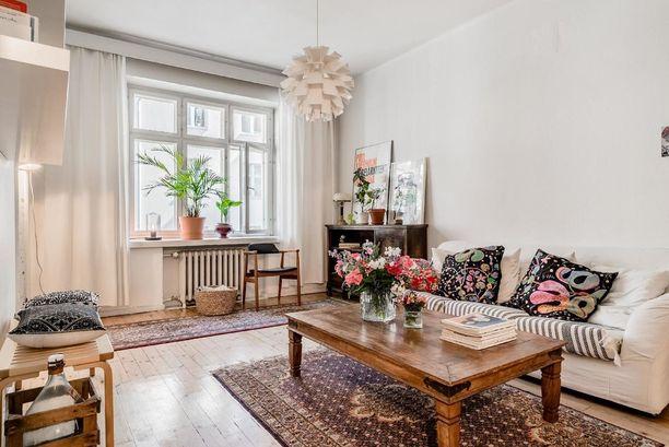 Trendikodissa yhdistellään nyt vanhaa ja uutta. Tässä olohuoneessa skandinaavinen valaisin ja vaaleat sävyt ovat saaneet parikseen antiikkityylisen sohvapöydän.