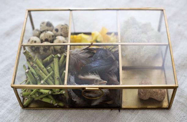 Kaunis lasilokerikko kätkee sisäänsä kukonsulkia, kanukan oksia, tetenarsissin kukintoja ja viiriäisen munia.