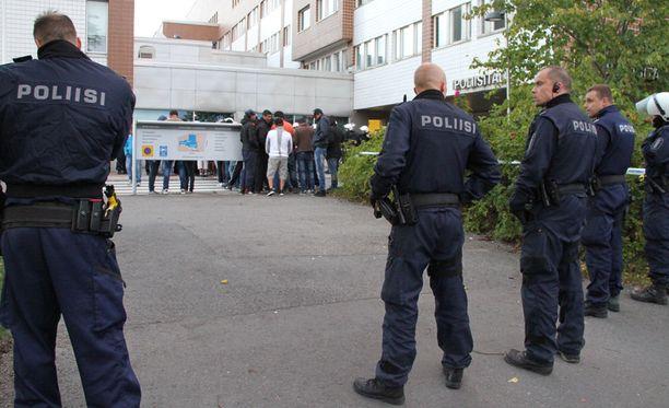 Poliisit turvaamassa järjestystä, kun turvapaikanhakijat marssivat ulos vastaanottokeskuksesta huonon ruoan ja asumisolojen takia Oulussa.