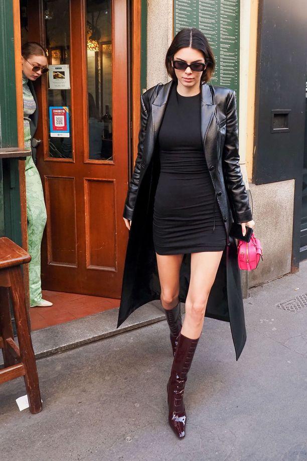 Kendall Jenner yhdistää simppelin, umpinaisen minimekon krokosaappaisiin ja pitkään nahkatrenssiin. Pitkä takki näyttää tyylikkäältä lyhyen helman parina.