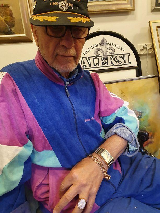"""Rauno, 80, pisti Speden kellon myyntiin. Pelaajalla pitää olla Raunon mukaan käsissään kultaa vaurauden merkiksi. Kuvassa miehen """"peliasu"""": 500 grammaa 18 karaatin kultaa."""