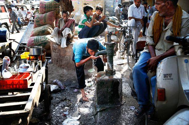 Nuori mies vilvoitti oloaan juomalla yleisestä kaivosta Delhin keskustassa.