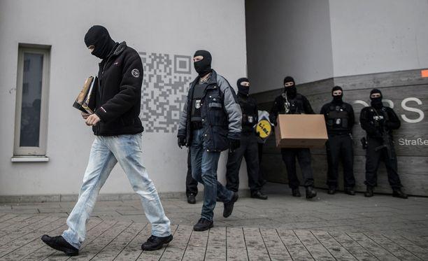 Naamioituneet poliisit kantoivat materiaalia ulos asuinrakennuksesta Berliinissä.