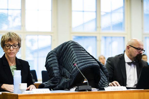 Kolmea hollantilaistaustaista miestä syytetään törkeästä huumausainerikoksesta. Yksi syytetyistä on kuvassa piiloutuneena takin alle. Kuvassa oikealla syytetyn asianajaja Mika Allén.