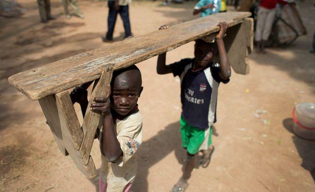 Lapset kantavat penkkiä pakolaisleirillä Banguin lähettyvillä. Yhä useampi paikallinen on joutunut paeta kodeistaan maan pahenevia levottomuuksia.