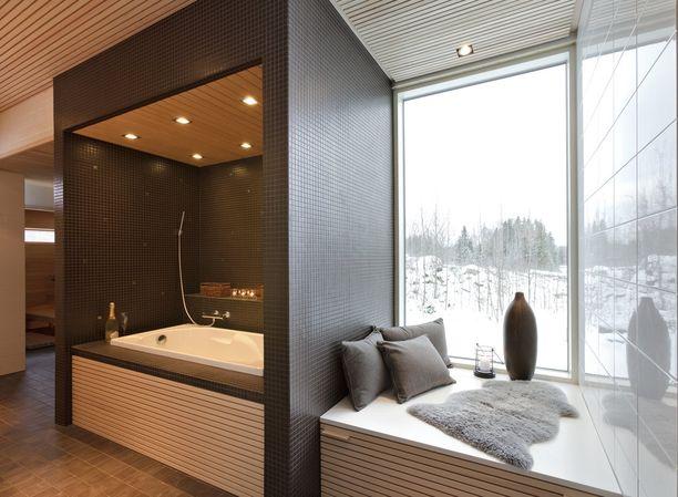 Erikoisemmatkin ratkaisut kannattavat! Minimalististen tummanpuhuvien seinustojen sisässä on ihana kylpypesä kattolamppuineen. Viereisestä ikkunasta voi ihastella maisemia.