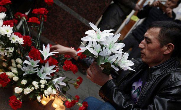 Mies laski kukkia Pietarin metroon tehdyn pommi-iskun uhreille.