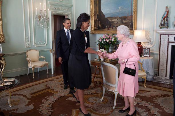 Vuonna 2009 Michelle Obama kätteli kuningatar Elisabetia ja myöhemmin myös otti tätä ystävällisesti kiinni hartioista.