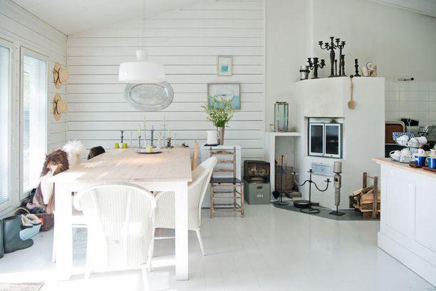 Korkea katto avartaa vaaleaa tilaa entisestään. Valkoinen lautalattia on kaunis yksityiskohta.