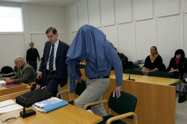 Matinkylän perhesurmaaja peitti takilla päänsä saapuessaan Espoon käräjäsaliin. Vierellä asianajaja Pekka Eriksson.