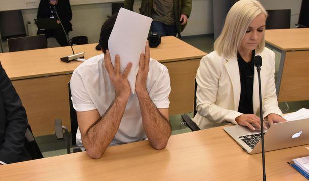 Mies istui käräjillä avustajansa Ulla-Maija Pöhön ja tulkin kanssa kasvot peitettynä.