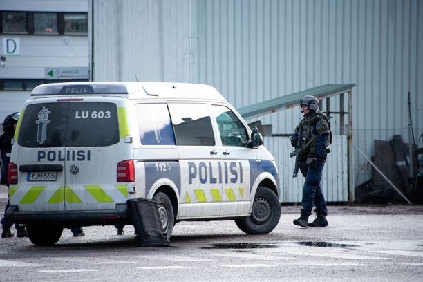 Poliisi piti esillä kiväärimallisia aseita, kun rikospaikkaa vartioitiin maanantaina.