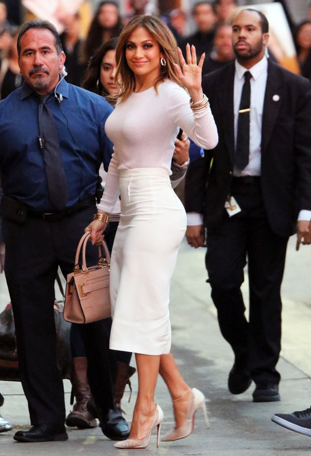 Jennifer Lopez korostaa muotojaan vetämällä korkeavyötäröisen hameen tiukan neuleen päälle.