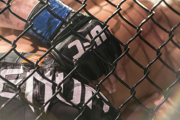 ERTJ5X UFC Cage fighters gloves grapple in the ring up against the cage in the Ultimate Fighting Championship mma bout