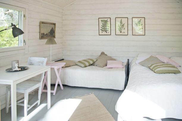 Toisen makuuhuoneen sisustuksessa rauhalliseen värimaailmaan on yhdistetty pilkahdus vaaleanpunaista.