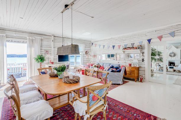 Ruokailuhuoneen puolella on jo enemmän väriä. Lippuviiri ja värikkäät sohvatyynyt tuovat tilaan leikkisyyttä.