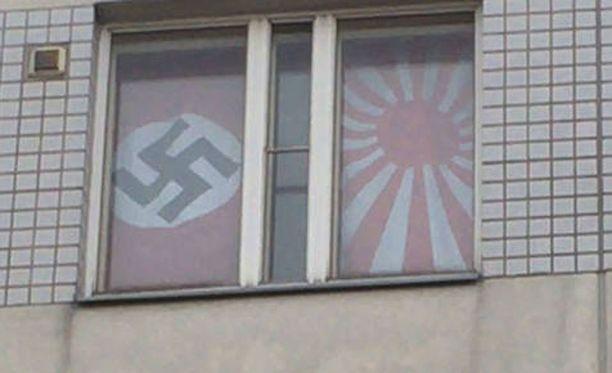 Kansallissosialistisen Saksan sekä Japanin keisarikunnan vanha sotalippu opiskelija-asunnon ikkunassa.