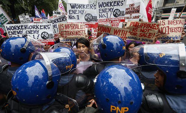 Mellakkapoliisit yrittävät pysäyttää mielenosoittajia Manilassa.