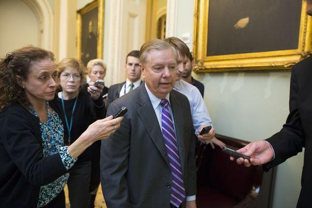 Republikaanisenaattori Lindsey Graham (kesk.) toimittajien ympäröimänä Washingtonissa 27.11.2018.