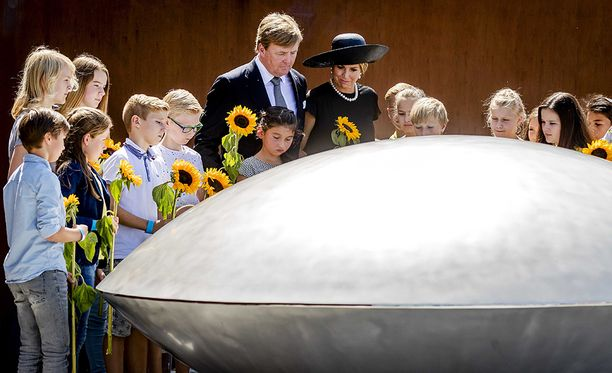 Hollannin kuningas Willem-Alexander ja kuniongatar Maxima lasten ympäröimänä muistolaatan luona, jossa on tragedian uhrien nimet.