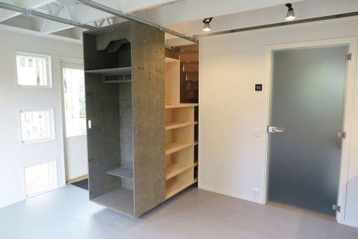 Vetokaappi on etuosastaan kiinnitetty kiskoilla kattoon. Takaosa liikkuu portaiden päällä. Kun kaapin vetää kokonaan ulos, lisää säilytystilaa löytyy portaiden alta.