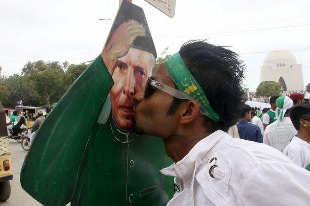 Mies pussaa maan ensimmäisen johtajan Muhammad Ali Jinnahin kuvaa.