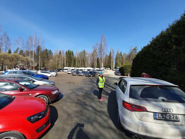 Parkkipaikka on täynnä autoja. Ihmisiä on 500 paikalla.