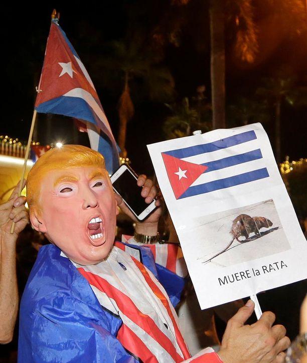 """Donald Trump -naamariin pukeutunut mies kantoi kylttiä, jossa luki """"rotta kuoli""""."""
