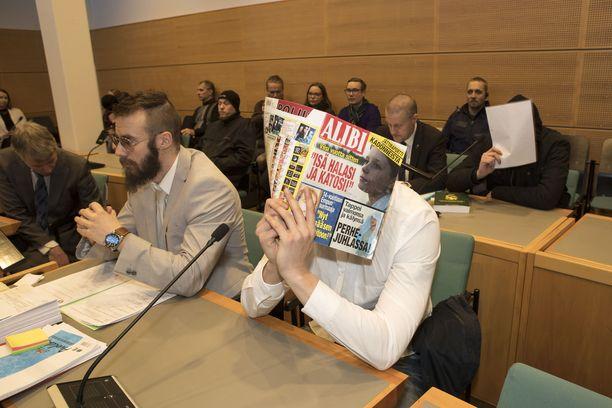 Epäillyt peittivät kasvonsa käräjäoikeudessa. Syyttäjä vaatii pääepäillylle elinkautista tuomiota.