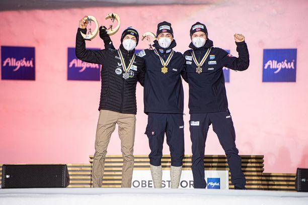 Ilkka Herola (vasemmalla), Jarl Magnus Riiber ja Jens Luraas Oftebro tuulettivat mitaleitaan lauantaina.