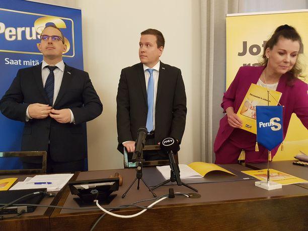 PS:n eduskuntaryhmän puheenjohtaja Ville Tavio (keskellä) ja varapuheenjohtajat Jani Mäkelä sekä Arja Juvonen valmistautumassa torstaina PS:n vaihtoehtobudjetin tiedotustilaisuuteen eduskunnassa.