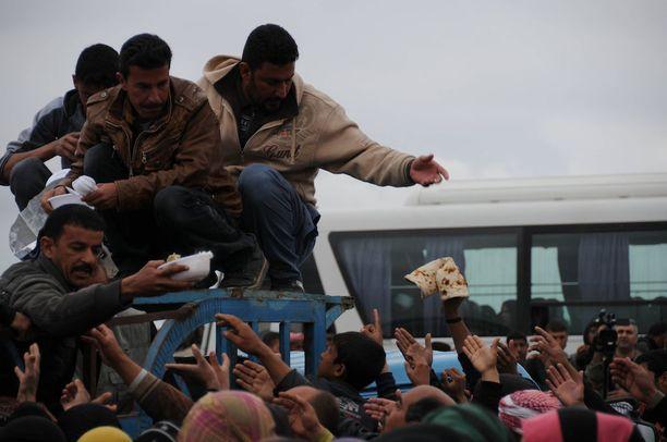 Länsi-Mosulista pakoon päässeet ihmiset saavat vapaaehtoistyöntekijöiltä leipää kaupungin ulkopuolella. Kuva maaliskuulta.